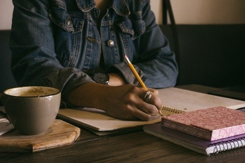 person writing at a desk with coffee