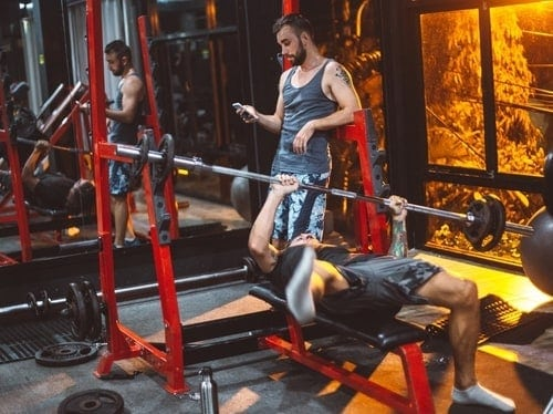 man not paying attention whilst his friend struggles with weights