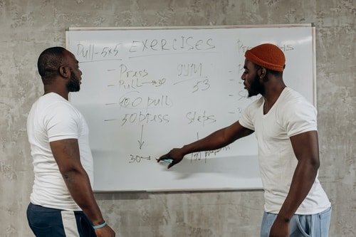 two men looking at exercises on a white board